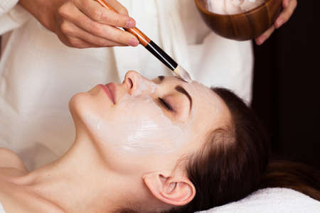 tratamientos faciales: Mujer hermosa con la m�scara facial en el sal�n de belleza. tratamiento de spa Foto de archivo