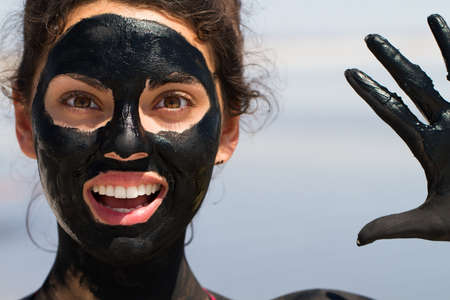 Beautiful young woman smiling with his mouth open in a mask out of clay