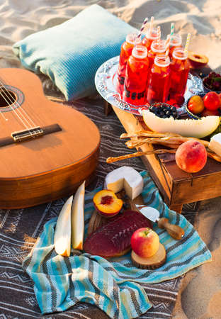 summer fruits: Picnic on the beach at sunset in the style of boho