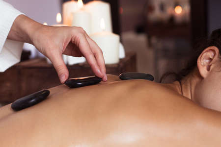 stone massage: Young woman getting hot stone massage in spa salon. Beauty treatment concept.
