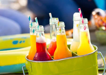 Bottles of lemonade , standing in a colorful green bucket on the beach in the summer sun. Picnic Time!