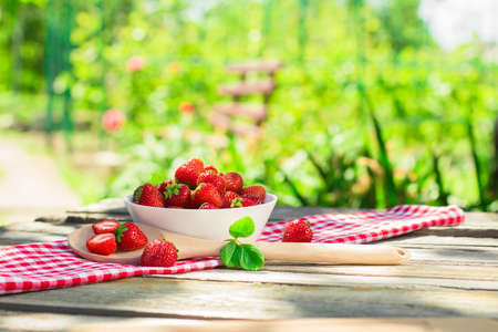 Spring fruits, strawberries in a paper bag on an old wooden background. Archivio Fotografico