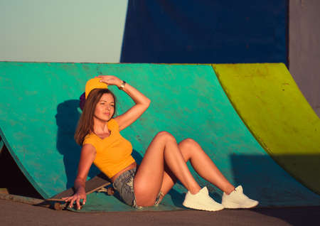swagger: Beautiful young woman sitting on a skateboard at the skate park Stock Photo