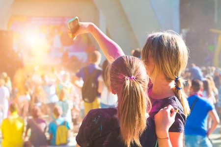 홀리 색상 축제 휴대 전화에 사진을 복용 젊은 여자 스톡 콘텐츠