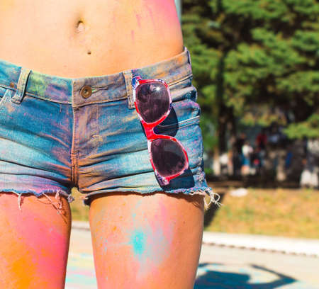 Girl in denim shorts at the festival of color Holi. Close up