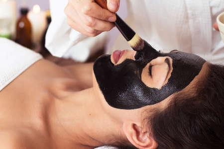 limpieza de cutis: Mujer hermosa con la máscara facial en el salón de belleza. tratamiento de spa Foto de archivo