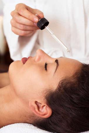 tratamiento facial: Mujer bonita que se relaja en el tratamiento de belleza. Masaje facial. Spa, centro turístico, la belleza y el concepto de salud Foto de archivo