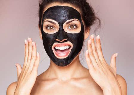 치료 검은 진흙의 얼굴 마스크에 젊은 아름 다운 여자. 스파 트리트먼트