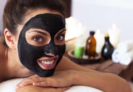 Jonge mooie vrouw in een masker voor het gezicht van de therapeutische zwarte modder. Spa-behandeling