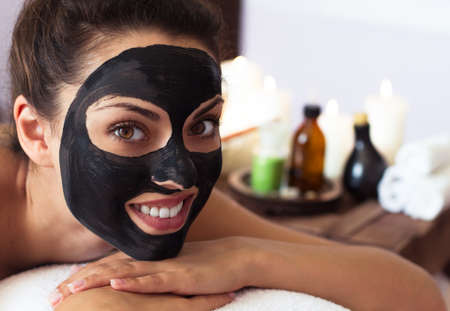 Young beautiful woman in a mask for the face of the therapeutic black mud. Spa treatment Banco de Imagens