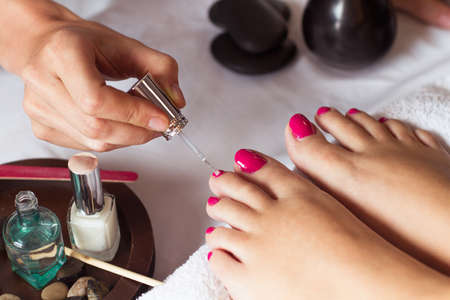 Vrouw in nagelsalon het ontvangen van pedicure schoonheidsspecialiste. close-up van vrouwelijke hand rusten op het witte doek
