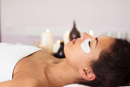 Mooie vrouw met een gezichtsmasker bij schoonheidssalon. Spa-behandeling Stockfoto - 47767030