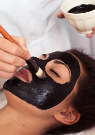 mud girl: Beautiful woman with facial mask at beauty salon. Spa treatment