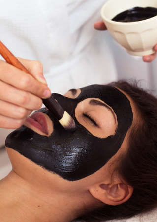 Mooie vrouw met een gezichtsmasker bij schoonheidssalon. Spa-behandeling Stockfoto