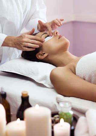 facial: Beautiful woman with facial mask at beauty salon. Spa treatment