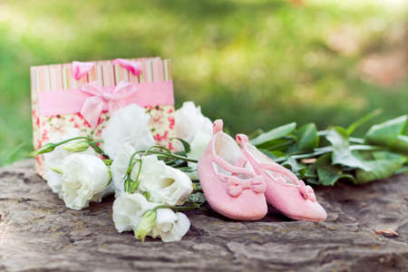 booties: Pink baby booties, flowers, a gift in the park. Pregnancy concept and a new life