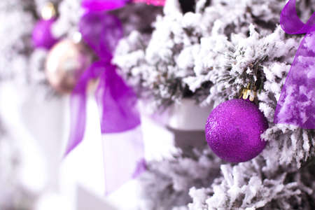 Purple Christmas ball hanging on a frosty tree in the snow.