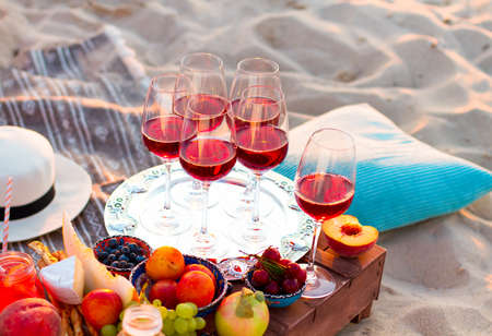 Glasses of the red wine on the sunset beach, picnic theme