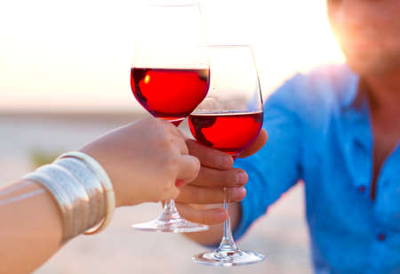 clang: Close-up of two human's hand with wineglasses red wine during sunset. Picnic theme. Stock Photo