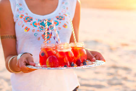 wristbands: Happy woman holds a dish with a drinks at sunset. Picnic theme