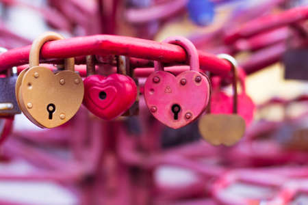 Vintage colorful padlocks heart shaped on blurred background, symbol of love Stockfoto
