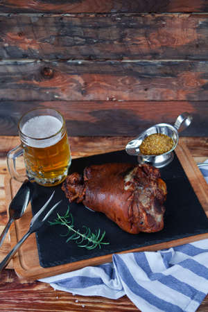 sause: Baked pork shank and honey sause and glass of beer on a dark wooden table. Horizontal view from above.