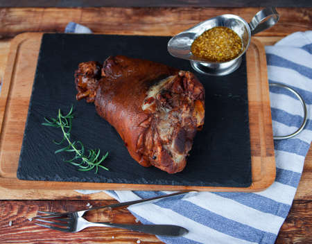 sause: Baked pork shank and honey sause on a dark wooden table. Horizontal view from above.