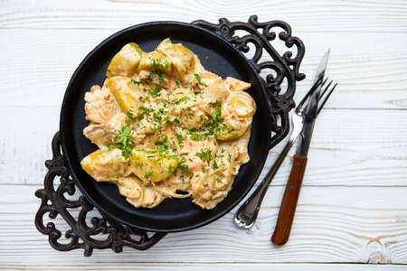 side order: Hot potatoes and red fish in creamy sauce giving in a pig-iron plate on a white wooden background