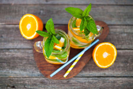 Cocktail. Orange juice with mint and ice on rustic wooden table