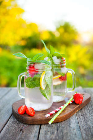 Cold summer drink with mint, strawberry and lemon on an old wooden table in a summer garden