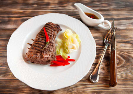 sause: Delicious beef steakes with chilli and red sause on white plate on wooden background. Top view Stock Photo