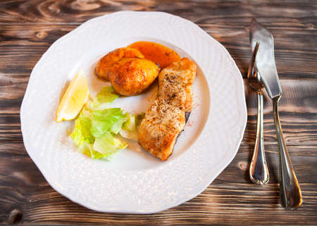 sause: Grilled fish with potatoes, slice of lemon and red sause on wooden background