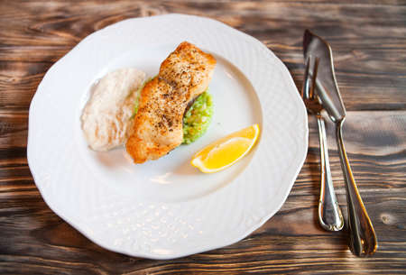 sause: Grilled Fish with slice of lemon and white sause on wooden background. Top view Stock Photo