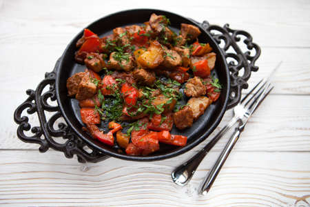 fryingpan: Hot meat with vegetable on frying pan on white wood background