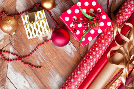 bolls: Rolls of Christmas wrapping paper with ribbons, gifts and bolls on wooden background Stock Photo