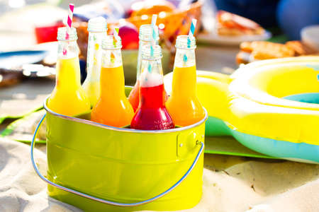 Bottles of lemonade , standing in a colorful green bucket on the beach in the summer sun. Picnic Time! Stock Photo