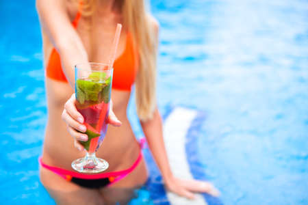 Woman hand with cocktail glass near swimming pool party. Close Up