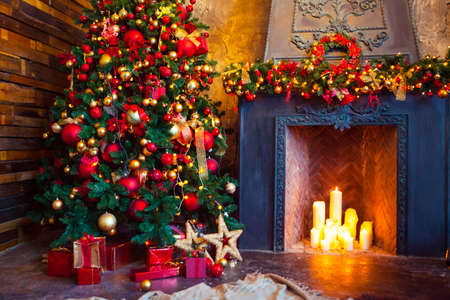 Christmas Room Interior Design, Xmas Tree Decorated By Lights Presents Gifts Toys, Candles And Garland Lighting Indoors Fireplace Фото со стока