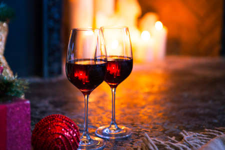 Two red wine in glass against the fireplace. Christmas Tree and Christmas gift boxes in the interior with a fireplace