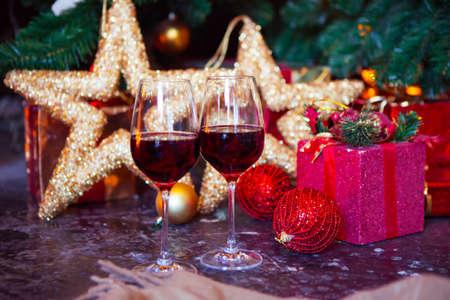 クリスマスの赤ワインを 2 杯木の背景には、クリスマス ツリーの装飾