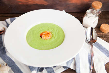 potage: Cream of asparagus soup with shrimp in a white bowl on a rustic background