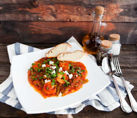 creole: Closeup of fresh shrimp creole with bread on old rustik background