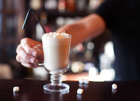 Bartender is making cocktail at bar counter at night club, Close Up. Concept about service and beverages.  Cocoa with marshmallow