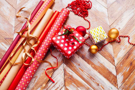 Rolls of Christmas wrapping paper with ribbons, gifts and bolls on wooden background Stock Photo