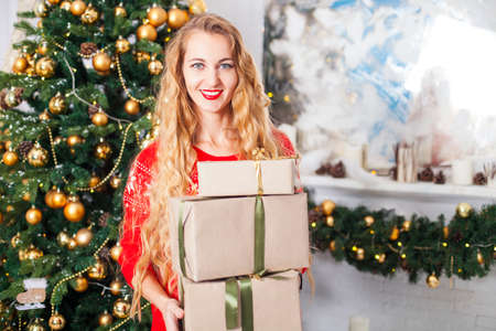 Portrait of happy young blondy woman with many christmas present box, at a Christmas decorations Stock Photo