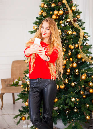 blondy: Young blondy pretty woman taking selfie near Christmas tree, Capturing a happy moment.