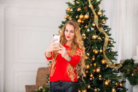 happy moment: Young blondy pretty woman taking selfie near Christmas tree, Capturing a happy moment.