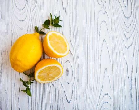 lemon slices: Juicy lemons with leaves on a white wooden background. Lemon slices. Fresh Lemon. Fresh citrus fruit background.