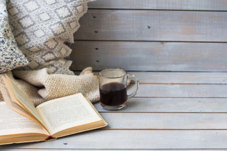 cosiness: Cushions, plaid, black coffee and old book on the light wooden background, closeup.