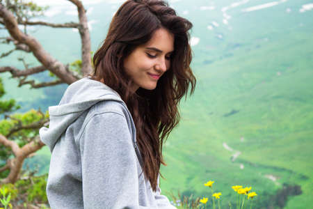 unrecognisable people: Portrait happy hipster Woman sitting on mountain top , close up Stock Photo